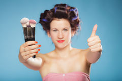 Woman in hair rollers holds makeup brushes Royalty Free Stock Images