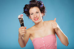 Woman in hair rollers holds makeup brushes Stock Images