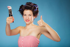 Woman in hair rollers holds makeup brushes Royalty Free Stock Photography
