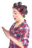 Woman with hair rollers looking in studio. Frightened woman looking for a manicure Royalty Free Stock Images