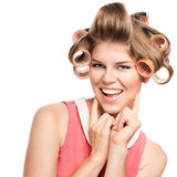 Woman in hair rollers. Portrait of happy blond Caucasian woman with hair curlers, isolated over white background. Young cheerful female model in studio Royalty Free Stock Photography