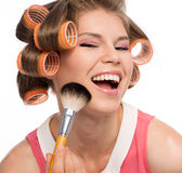 Woman in hair rollers. Portrait of young cheerful female in curlers applying rouge with makeup brush. Beautiful blond Caucasian female happy smiling, isolated on Stock Photography