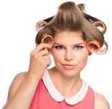 Woman in hair rollers. Shoot of confused female in curlers thinking about curly hairdo. Beautiful blond Caucasian woman Isolated on a white Stock Photo