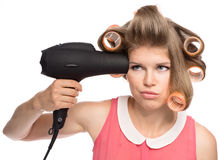 Woman in hair rollers. Stressed woman in hair curlers preparing for a date. Pretty blond female model with hairdryer. Isolated over white background Stock Image
