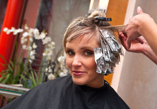 Woman in hair salon. Woman coloring her hair in hairdresser salon Stock Images