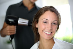 Woman at the hair salon. Woman having her hair dried by hairdresser Stock Image