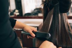 Woman at the hair salon getting her hair styled. Hairdresser using a hair straightened to straighten the hair. Hair stylist working on a woman`s hair style at Stock Images