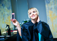 Woman in hair salon photographing herself Royalty Free Stock Photography