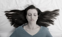 Woman With Hair Spread on Bed Stock Photo