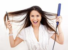 Woman with hair straightener Stock Photo