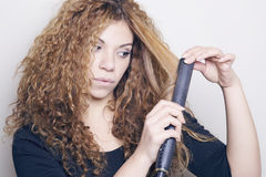 Woman with a hair straightener. Woman with a hair straightener, ironing her hair Stock Image