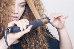 Woman with a hair straightener. Woman with a hair straightener, ironing her hair Stock Photography