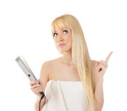 Woman with hair straighteners Royalty Free Stock Photography