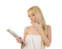 Woman with hair straighteners looking surprised Royalty Free Stock Image