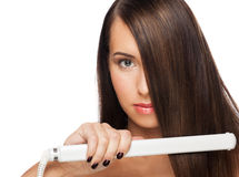 Woman with hair straightening irons Royalty Free Stock Photo