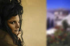 Woman with hair up. Close to a wall and view in the background Stock Photo