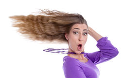 Woman with hair in wind. Party atmosphere - woman with hair in wind isolated in purple royalty free stock image