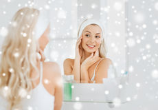 Woman in hairband touching her face at bathroom Royalty Free Stock Images