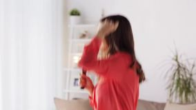 Woman with hairbrush singing and dancing at home stock video footage