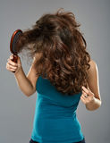 Woman with hairbrush, studio shot Stock Image
