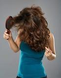 Woman with hairbrush, studio shot Stock Image