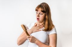 Woman with hairbrush is suffering from hair loss. Isolated on white background royalty free stock photo