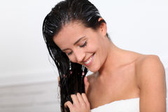 Woman and haircare. Beautiful woman applying hair conditioner Royalty Free Stock Photos