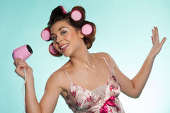 Woman in haircurlers with hairdryer Royalty Free Stock Images