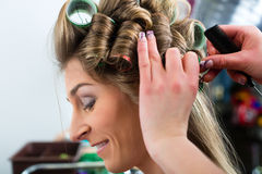 Woman at the hairdresser curling hair Stock Photo