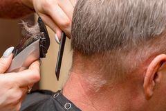 Woman Hairdresser cuts man`s hair with electric clipper trimmer stock photos
