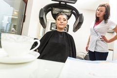 Woman in hairdresser, drying hair under machine Royalty Free Stock Image