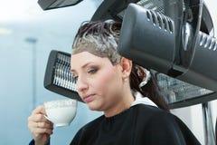 Woman in hairdresser, drying hair under machine Stock Photo