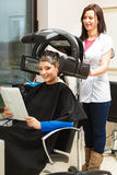 Woman in hairdresser, drying hair under machine Stock Photo