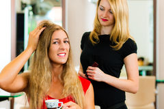 Woman at the hairdresser getting advise. On her hair styling, the girls are drinking Cappuccino royalty free stock images