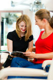 Woman at the hairdresser getting advise. On her hair styling or new hair color royalty free stock photo