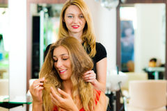 Woman at the hairdresser getting advise. On her hair styling royalty free stock photos