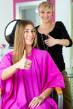 Woman at the hairdresser getting advise. On her hair styling royalty free stock image