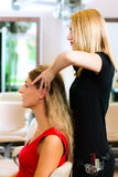 Woman at the hairdresser getting a head massage Stock Photography