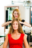 Woman at the hairdresser getting a head massage royalty free stock image