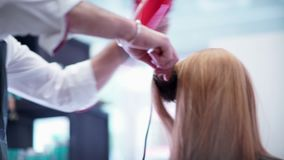 The woman at the hairdresser. Hairdresser used a brush and dryer. stock video