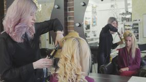 Woman hairdresser making curls at blond hair with curling irons at beauty salon. stock video footage
