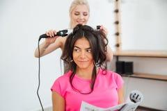 Woman hairdresser making hairdo using curling iron Royalty Free Stock Photo