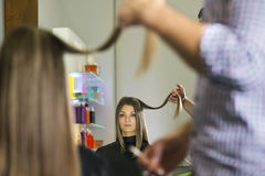 Woman in hairdresser shop cutting long hair Royalty Free Stock Images