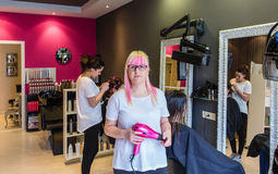 Woman hairdresser standing in hair and beauty Royalty Free Stock Photos