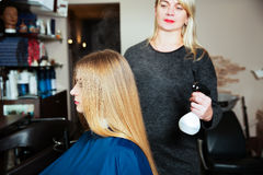 Woman hairdresser uses spray for hair Stock Images