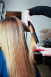 Woman hairdresser using curling iron. Royalty Free Stock Photography
