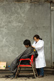 Woman hairdresser working with a customer man in the streets of Stock Photography