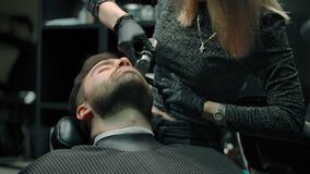 Woman hairdresser works with trimmer with a beard of a client.