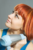 Woman with hairdryer Stock Images