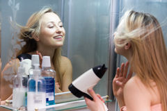 Woman hairdryer bathroom. Portrait of young smiling girl drying her hair in bathroom and looking at mirror royalty free stock photo